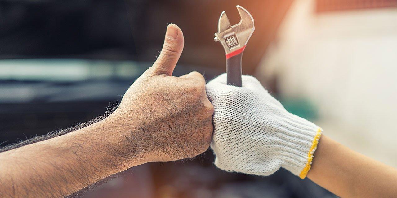 Zwei Hände: eine mit Schraubschlüssel, eine mit weißem Handschuh