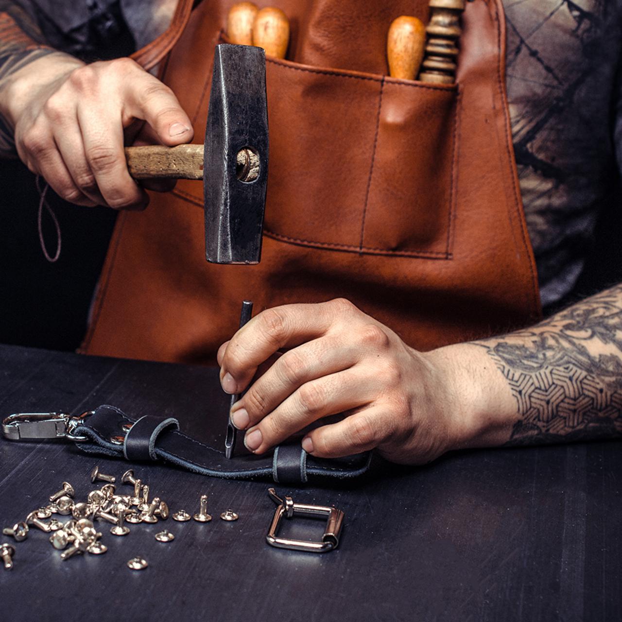 Handwerker mit Hammer stanzt Löcher in einen Gürtel