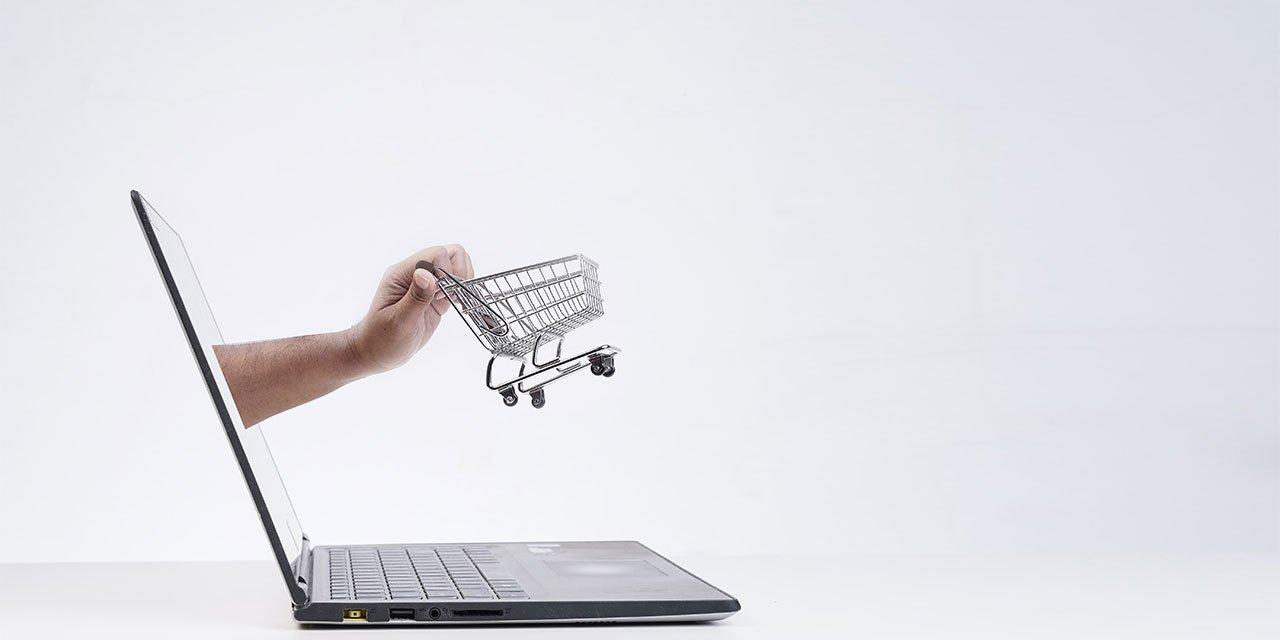 Laptop aus dem eine Hand mit Einkaufwagen raus kommt
